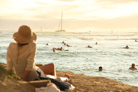 woman looking at people swimming in beach during sunset