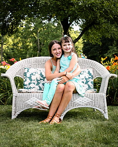 child in teal sleeveless shirt and pants sitting on woman lap in teal sleeveless dress sitting on white wicker sofa