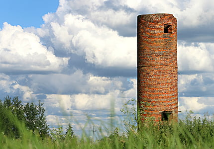 brown stoned tower surrounded by green grass field