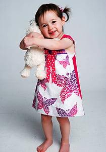 girl wearing dress hugging hear plush toyt