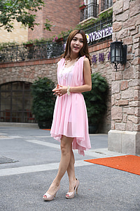 woman wearing pink V-neck sleeveless pleated dress