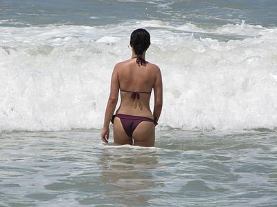woman wearing maroon bikini facing the ocean
