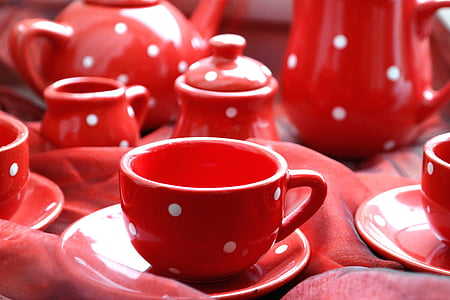 selective focus photography of red-and-white polka-dot ceramic teacup on saucer