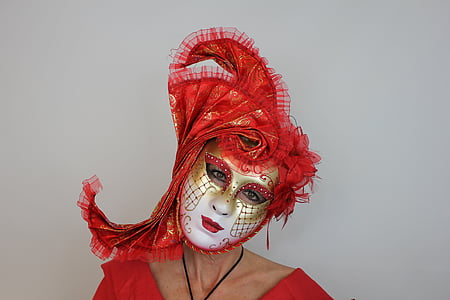 person wearing red and white masquerade mask