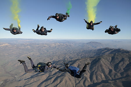 seven person performing on the air with parachute