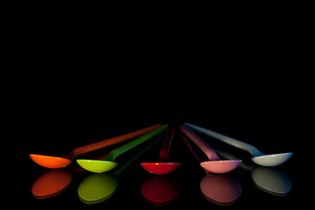 five assorted plastic spoons isolated with black background
