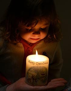 girl facing at lit pillar candle