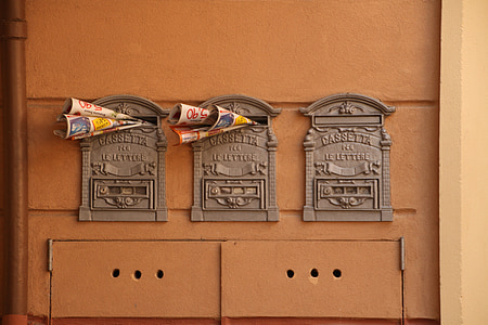 three antique gray mailboxes