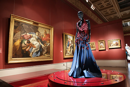 mannequin wearing red and blue dress near paintings