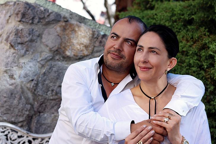 man and woman wearing white dress shirts sitting near boulder