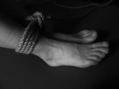 grayscale photo of feet tied with rope