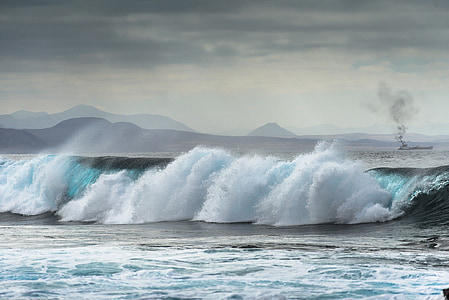 waves of body of water under gray clouds