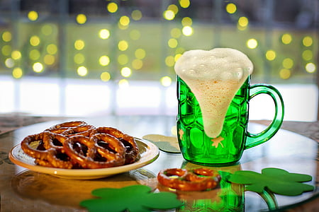 green glass beer stein and pretzel filled white plate