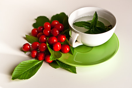 green hear near red fruit and white ceramic cup