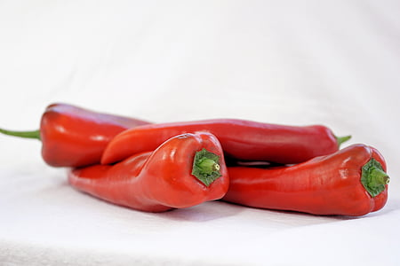 selective focus photography of four red jalapenos