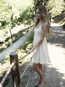 woman wearing white floral tank dress standing beside beige and brown rope railing