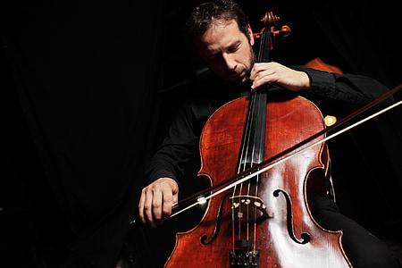 man sitting playing cello