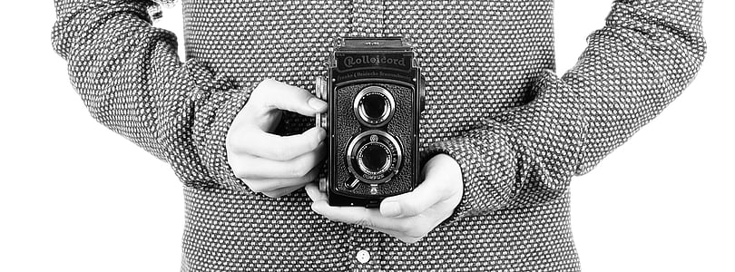 grayscale photography of person holding classic camera