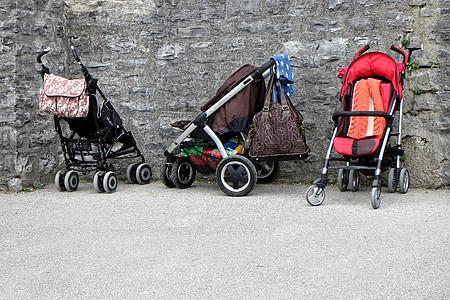 three empty strollers beside wall