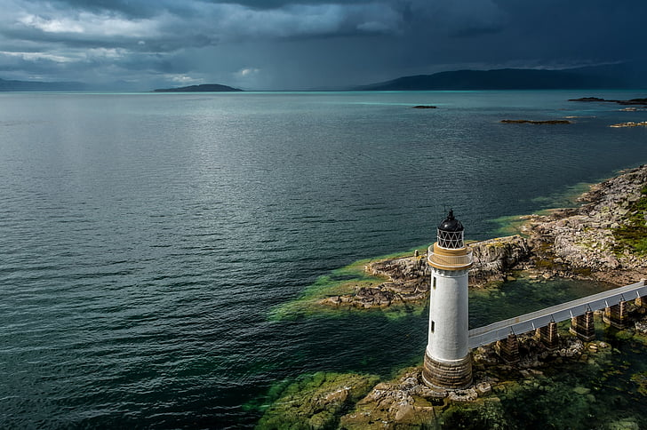 white lighthouse near seashore during twilight
