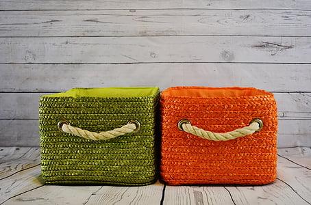 green and orange fabric hampers on gray flooring