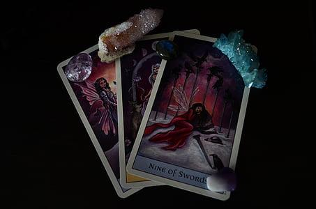 three tarot cards with gemstones