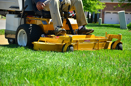 person sitting on yellow zero-turn lawn mower
