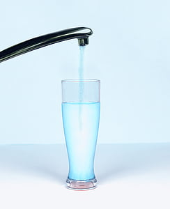 clear drinking glass under gray steel faucet