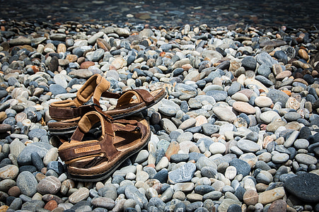 pair of brown sandals on gray stones