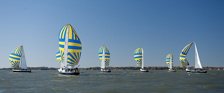 blue-and-yellow sailboats on body of water