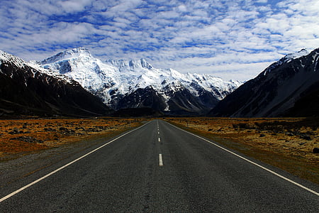 road near mountain covered by snows