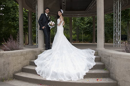 man in black suit standing beside woman wearing white wedding dress