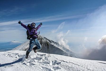 man wearing purple jacket near mountain under blue sky during daytime