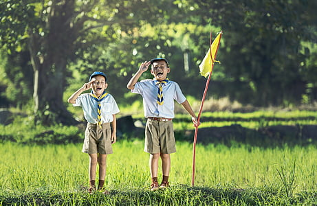 boy's scouts standing on green grass while holding flag