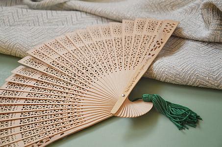 beige hand fan beside beige knitted textile