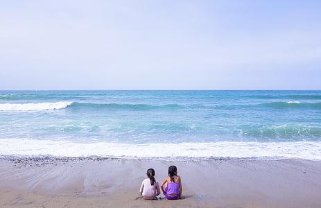 two girls sitting on seashore