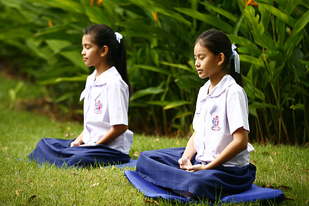 two girls in uniforms meditating