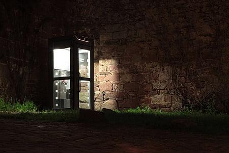 phone booth near brown brick wall