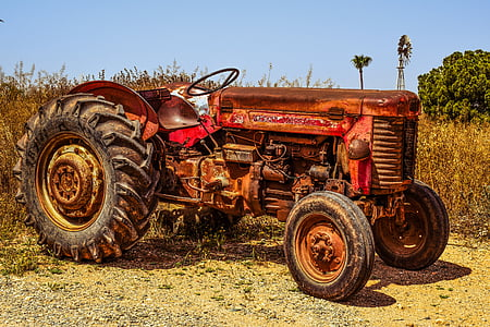 red and brown tractor near withered plant