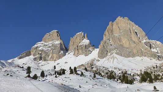 snow-covered mountain with trees under blue sky