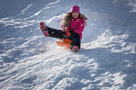 woman riding on orange board sliding on snow filled mountain