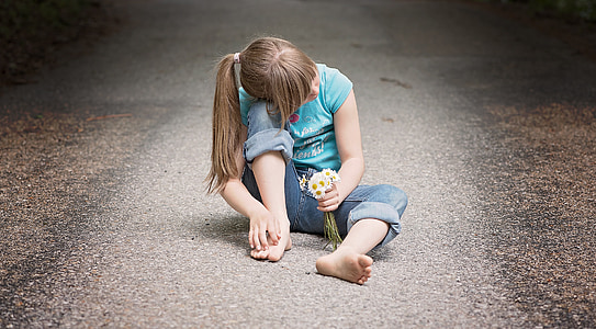 girl sitting in the middle of the road