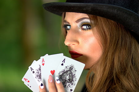 woman wearing black hat holding ace playing cards