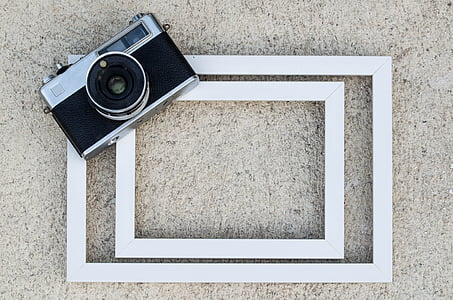 gray and black SLR camera on white wooden surface
