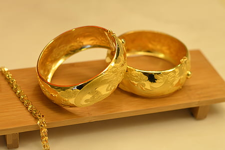 two gold-colored rings on brown wooden platform