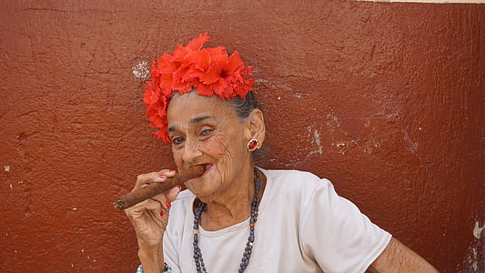 woman wearing white shirt holding cigar