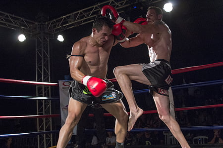 two male Muay-Thai fighters inside ring fighting