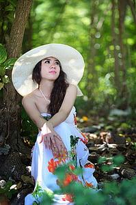 women's white halterneck dress sitting under tree