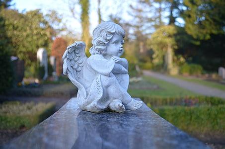 tilt-shift lens photography of sitting white cherub figurine