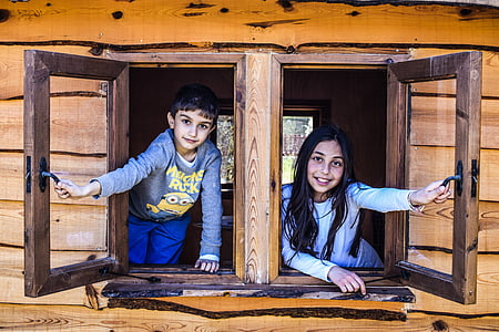 boy and girl looking holding two brown wooden window frames